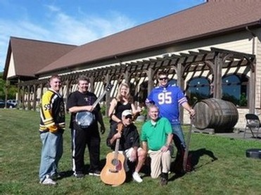Photo of the band members in The Galtee Mountain Boys in front of Keuka Spring Vineyards' tasting room on a sunny day