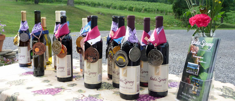 Photo of an assortment of Keuka Spring wines, with medals they won in competitions draped over their necks